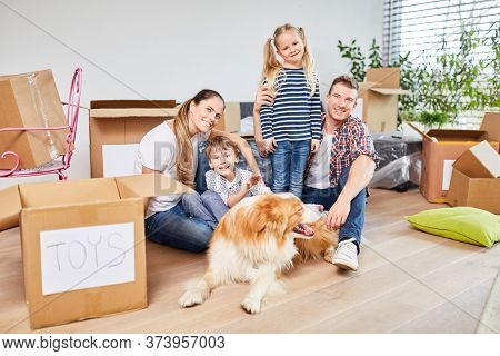 Happy family with children and dog moving with many moving boxes