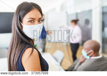 Young business woman wearing a face mask because of Covid-19 and corona virus giving a presentation in the office