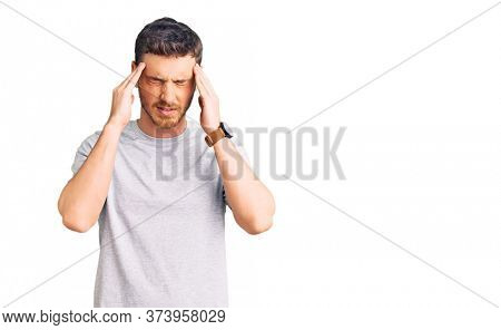 Handsome young man with bear wearing casual tshirt with hand on head for pain in head because stress. suffering migraine.