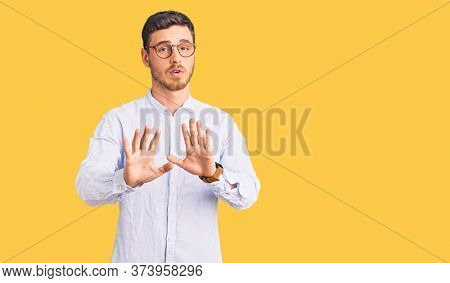 Handsome young man with bear wearing elegant business shirt and glasses moving away hands palms showing refusal and denial with afraid and disgusting expression. stop and forbidden.