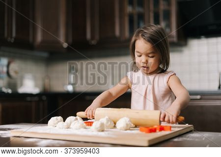 Curious Beautiful Little Girl Is Rolling The Dough Out With Wooden Rolling Pin At The Table In Kitch
