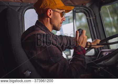 Caucasian Male Truck Driver Communicating On Two Way Radio Inside Of Vehicle Cab.