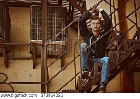 Handsome young man in casual clothes sits on a metal industrial staircase. Urban grunge style. Male fashion.