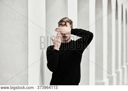 Art portrait. Handsome young man model in black pullover posing next to white columns in the old town, covering his face with his hands. Men's style, beauty. Fashion shot.