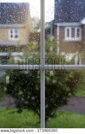 Raindrops On Window Glass In Rainy Day With Blurry Tree And House Background, View Looking Trough Wi