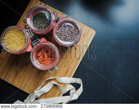 Four Glass Jars Filled With Dry Food Ingredients Such As Gluten Free Red Lentil Pasta And Black Lent