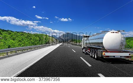 Big Fuel Gas Tanker Truck On Highway Against The Backdrop Of A Mountain Landscape.