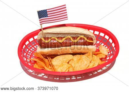 Hot Dog. Hot Dog with Potato Chips and an American Flag in a plastic basket. Isolated on white. Room for text. Holiday Picnic Food.