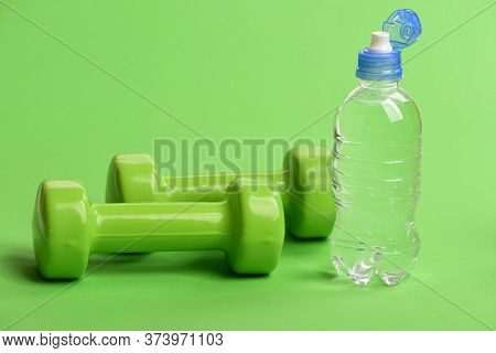 Water Bottle Near Lightweight Barbells, Close Up. Athletics Concept