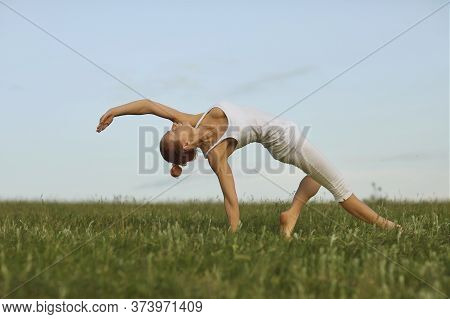 Yoga Balance In Nature. Graceful Young Woman Practicing Backbend Yoga Pose On Green Meadow. Fit Girl