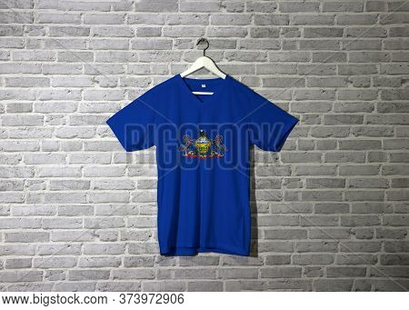 Pennsylvania Flag On Shirt And Hanging On The Wall With Brick Pattern Wall. Coat Of Arms Of Pennsylv