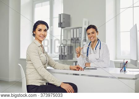 Smiling Female Patient At Consultation With Woman Doctor Sitting At Table In Office Clinic.