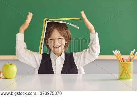 Back To School. Cheerful Little Boy Hiding Under Book, Playing Silly Game At Desk In Classroom.