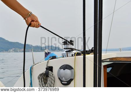 Close-up Of The Hand With Blue Nail Polish Of A Female Skipper Pulling A Rope While The Sailboat Goe