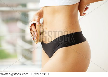 Womans Arm Holding Dry Brush To Top Of Her Stomach, Cellulite Treatment And Dry Brushing.