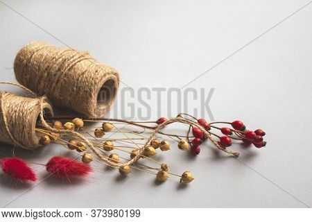 Creative Composition With Natural Jute Twine Roll - Linen Or Cannabis, With Dry Flowers On Light Bac