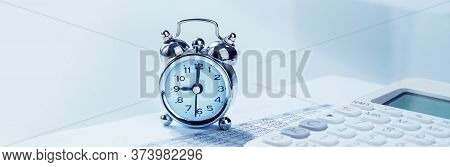 Alarmclock With Calculator On Financial Paperwork. Finance And Business Concept Blue Banner. Deadlin