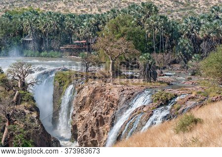 Part Of The Epupa Waterfalls In The Kunene River. Buildings, Baobab And Makalani Palm Trees Are Visi