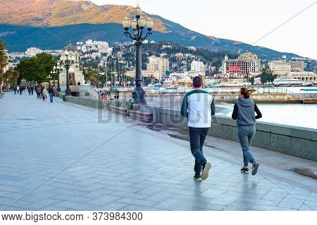 Yalta, Crimea - April 3, 2018: Couple Jogging At Sea Promenade, Walking Tourists, Church And Sunset