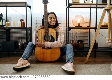 Woman sitting on the floor and hugs the guitar