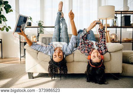 Happy women enjoys listening to music upside down