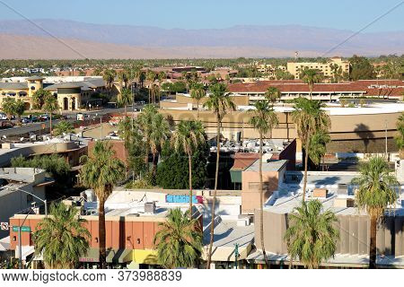 June 22, 2020 In Palm Springs, Ca:  Palm Trees Surrounding Buildings With Barren Mountains Beyond Ta