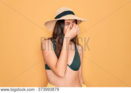 Young beautiful girl wearing swimwear bikini and summer sun hat over yellow background tired rubbing nose and eyes feeling fatigue and headache. Stress and frustration concept.