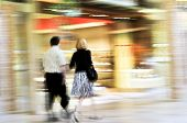 Couple shopping in a mall panning shot intentional in-camera motion blur poster