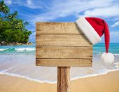 tropical beach wooden signboard with Christmas hat poster