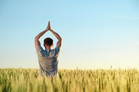 Adult Man Stands On A Field In Tall Grass Doing Yoga During Sunrise. Mental Health, Connection With