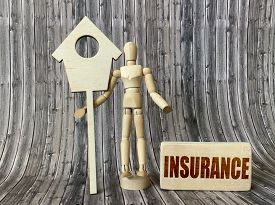 A Wooden Man Stands Next To A Wooden House, A Wooden Cube With The Words Insurance On A Wooden Backg