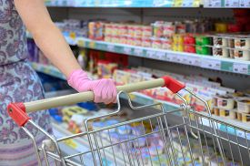 Woman In Protective Glove With A Shopping Cart In A Supermarket. Selective Focus On The Hand. Pandem