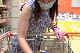 Woman Wears Protective Mask And Gloves While Shopping At Supermarket. Pandemic Times Shopping. Horiz