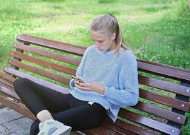 Beautiful Teenager Girl Sitting On The Bench In A Park. Caucasian Blonde Girl Holding Smartphone. Ga