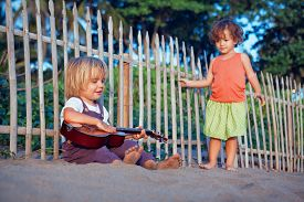Little Happy Boy Have Fun, Play Music On Hawaiian Guitar Ukulele For Small Baby Girl, Enjoying Sunse