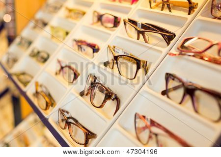 Eyeglasses shades and sunglasses in optician's shop poster