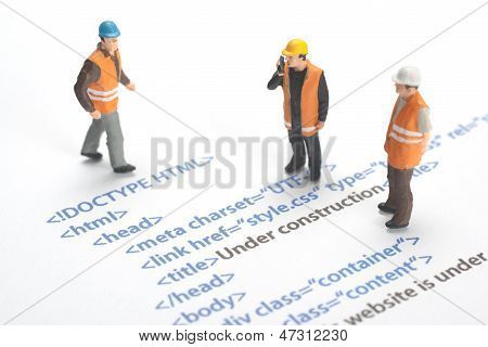 Printed HTML code of website (internet page) under construction. Construction worker figurines working on code. poster