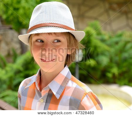 Summer portrait of cheerful funny carefree little boy in hat outdoor
