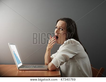 tired young businesswoman working with laptop