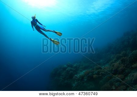 Young woman freediving in a sea over coral reef