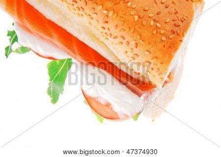 salmon sandwich on white with green salad and tomatoes