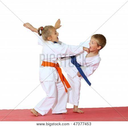 Girl in a kimono hits hand boy in a kimono hits a foot