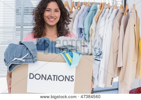 Pretty volunteer holding clothes donation box