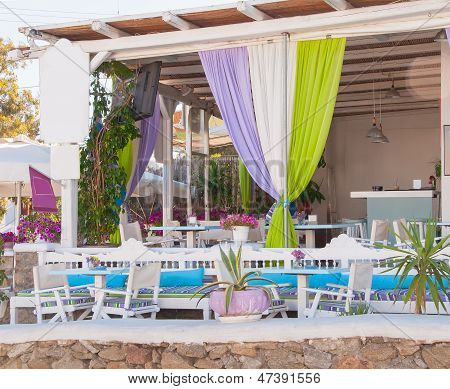 Restaurant On The Narrow Street Of The Island In Greece With Colorful Curtains