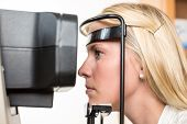 Patient and auto refractometer at optician or optometrist for scanning poster