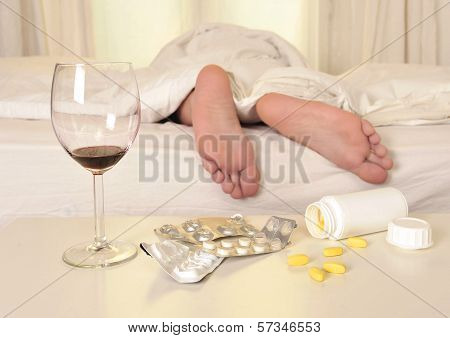 Feet On Bed Of Sleeping Man Suffering Hangover And Headache