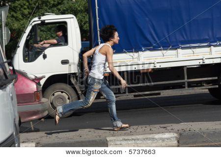 Girl Runs On Road Among Cars