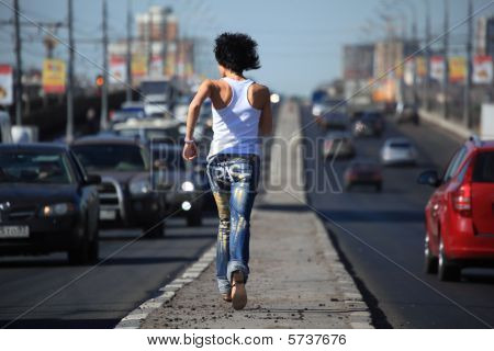 Girl Runs On Highway Middle In City, View From Back