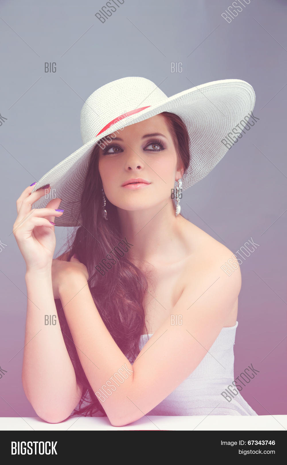 c5048963 Portrait of a beautiful young brunette woman. Wearing white hat over long  loose curly hair