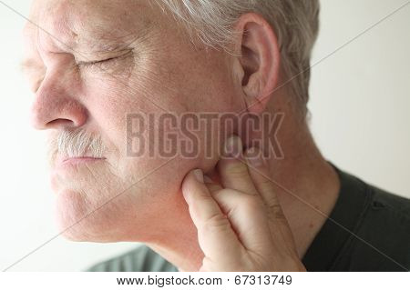 Man suffering from jaw joint pain